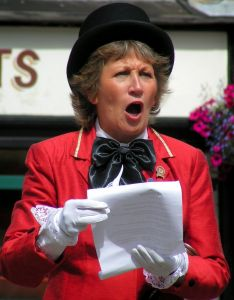 A female Town Crier delivers the news.  Stock photography